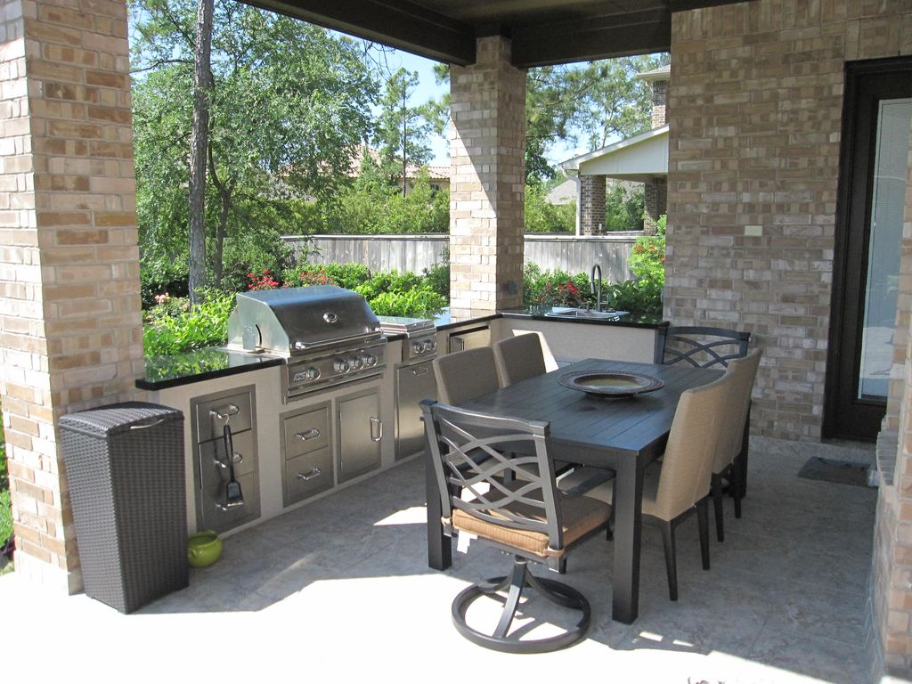 This small outdoor kitchen features a black countertop on the bar counter while the dining table set looks stylish.