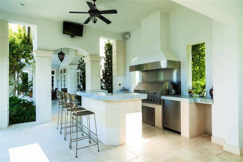 This white outdoor kitchen boasts a marble counters and a breakfast bar for four.