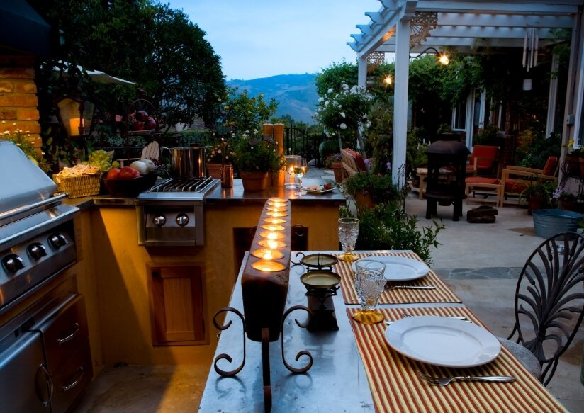 This outdoor kitchen offers a very romantic lighting along with stylish bars and counters.