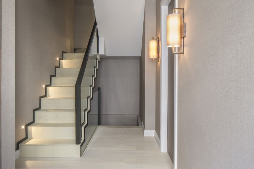 Straight staircase accented with black lining and stair lights along the gray hallway illuminated by wall sconces. It also has glass balustrade lined with deep gray handrail.
