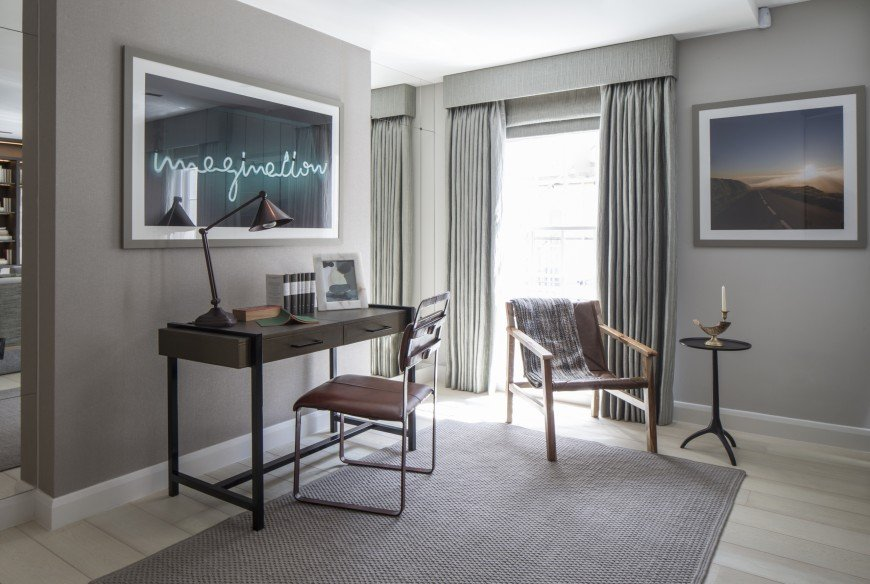 Gray home office designed with a landscape and statement wall art mounted above the dark wooden desk paired with a leather metal chair. There's a wooden lounge chair and round side table in the corner and by the full height window.