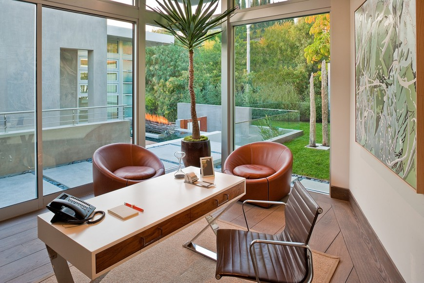 Glazed home office accented with a tall indoor plant in between coral round back chairs. It has a blush office desk with wooden drawers and a brown leather chair.