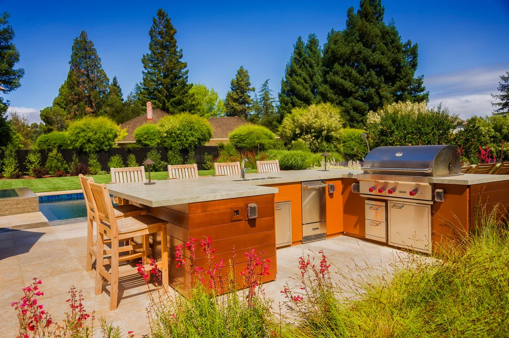 Outdoor kitchen with a large bar counter. There's a wide space for a breakfast or drinking bar.