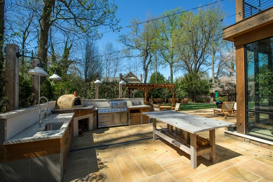Large outdoor kitchen featuring an L-shape bar counters equipped with marble countertops.