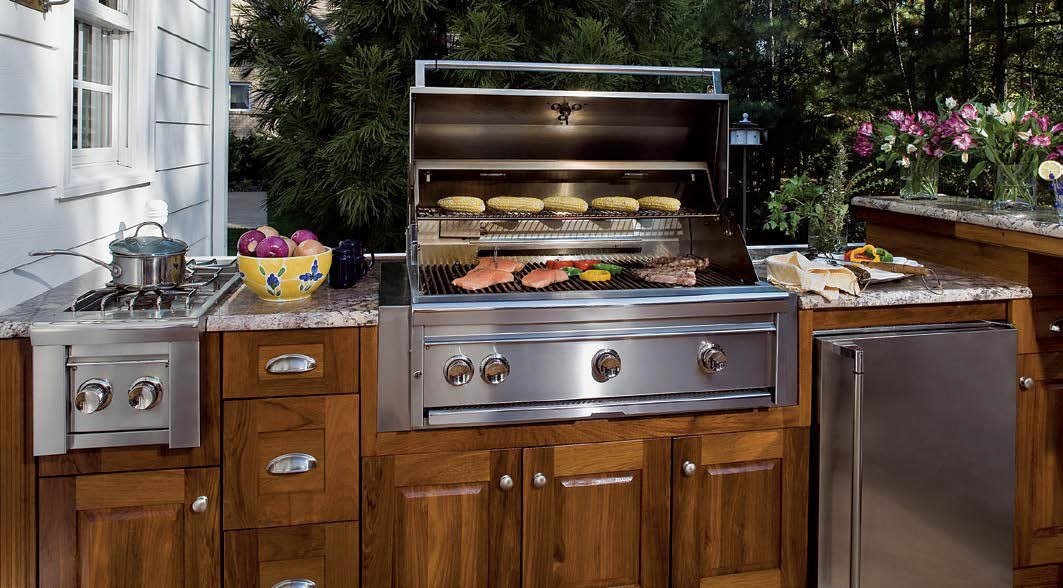 This outdoor kitchen features a classy bar with marble countertops along with top-of-the-line appliances.
