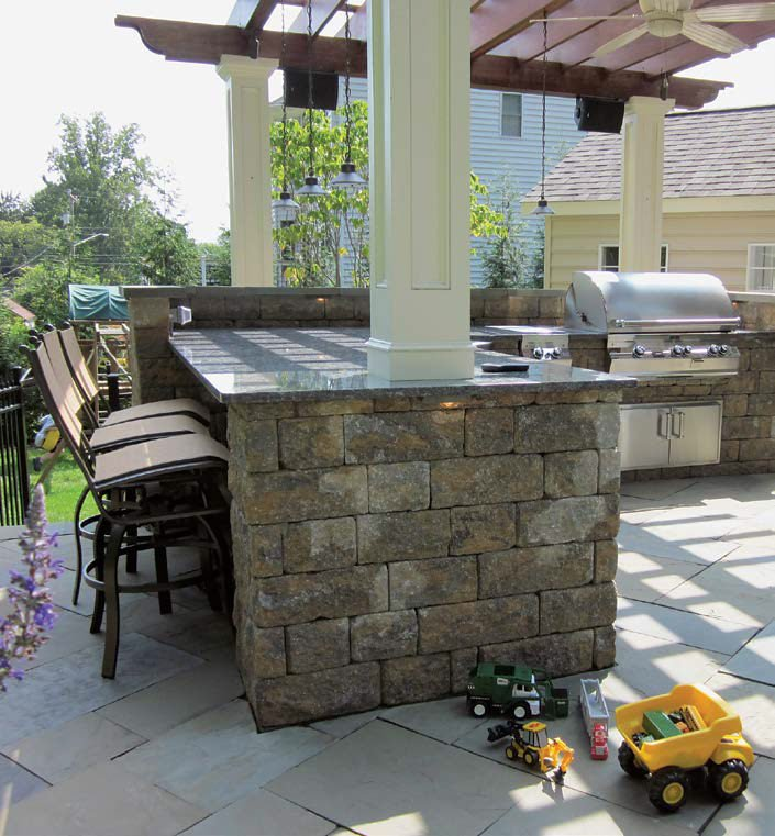 Close up look at the outdoor kitchen's stone bick bar with granite countertop. The counter provides space for a small breakfast bar.