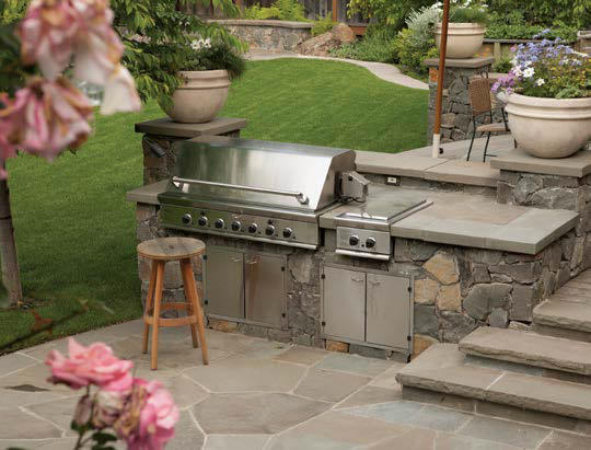This outdoor kitchen boasts a bar made of stones and smooth countertop.