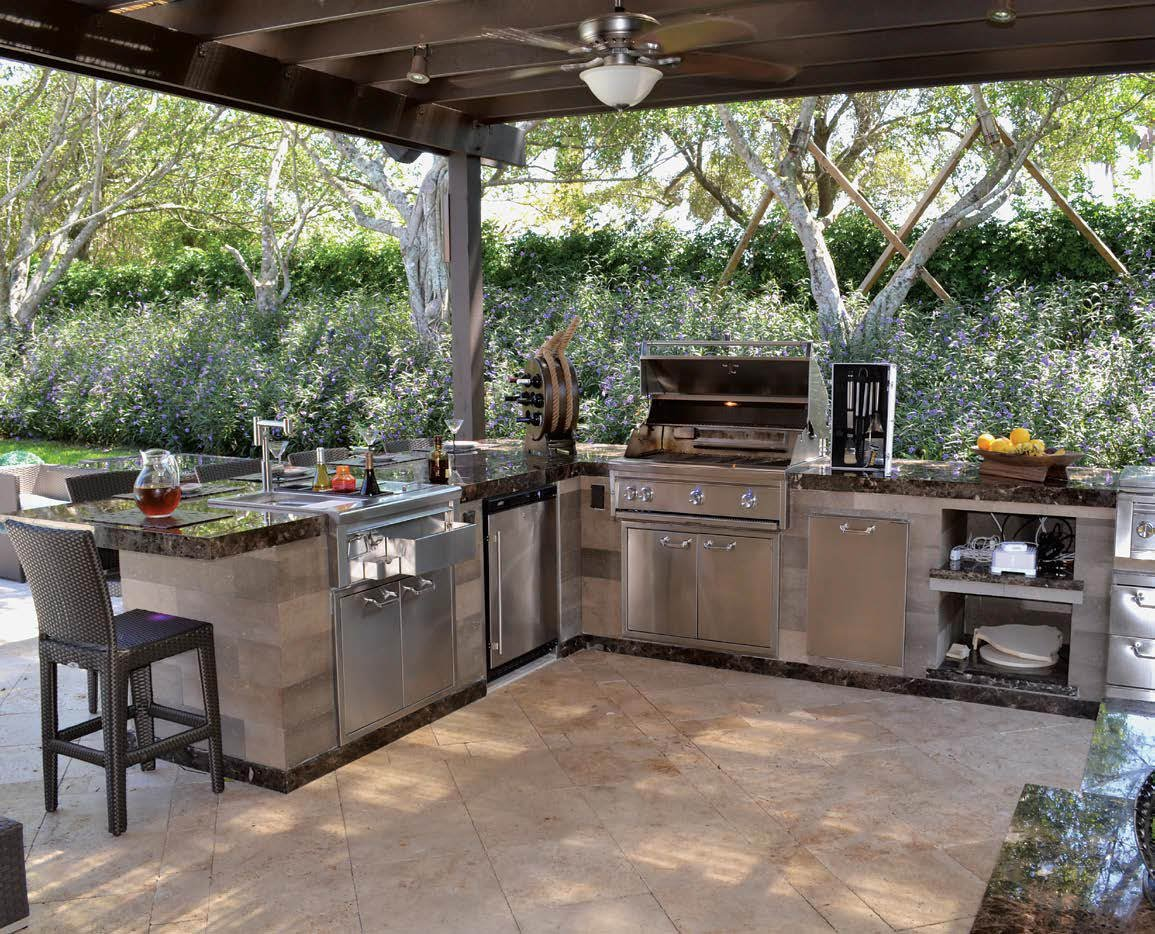 This outdoor kitchen boasts an L-shaped bar setup with granite countertops equipped with stainless steel appliances.