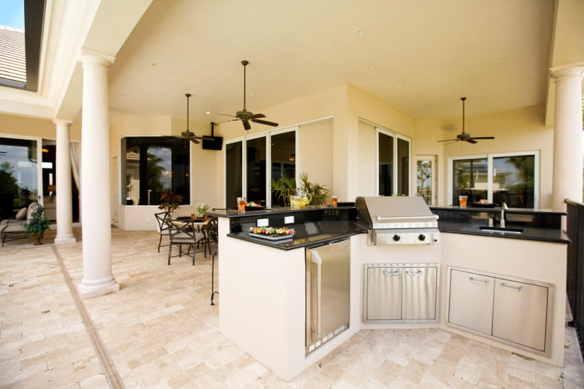 Large white outdoor kitchen featuring a bar with a black countertop along with a dining table set nearby.