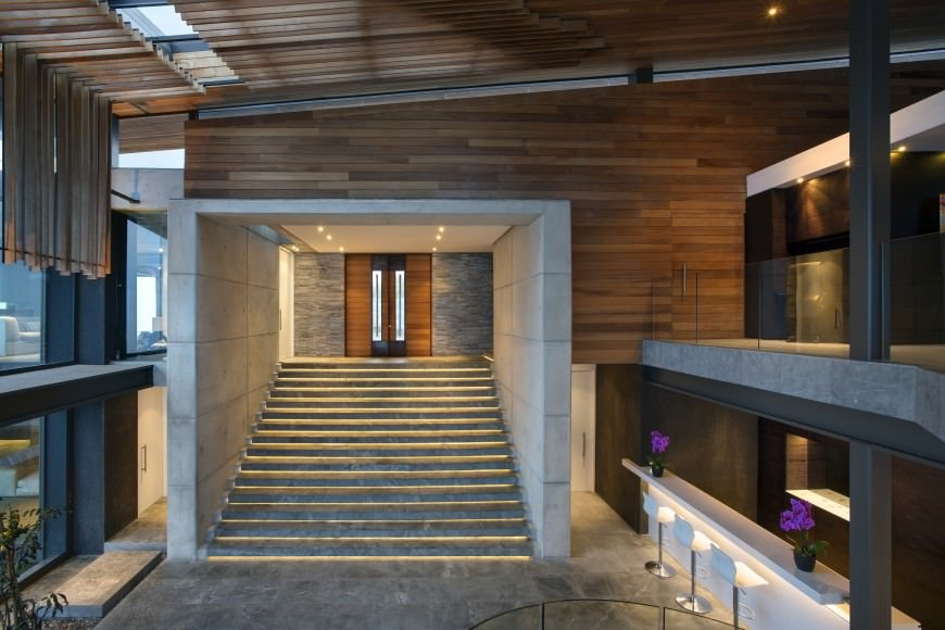 Fabulous entryway with a wooden front door that leads to the concrete staircase framed with white tiled walls and illuminated by recessed lighting.