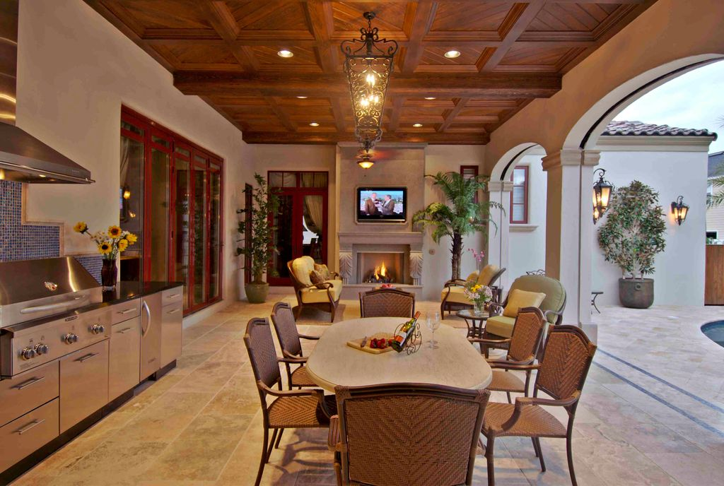 Elegant outdoor kitchen featuring a dining table set and a living set near the fireplace, all lighted by glamorous lighting.