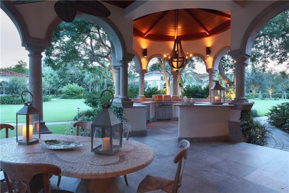 A glamorous outdoor kitchen with a galley type bar and counter setup lighted by pendant and wall lights.