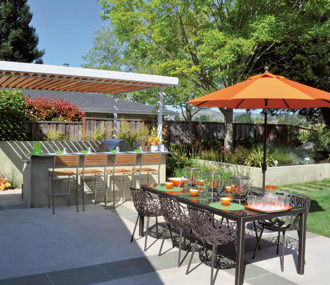 This outdoor kitchen features a drinking bar and a dining table set.