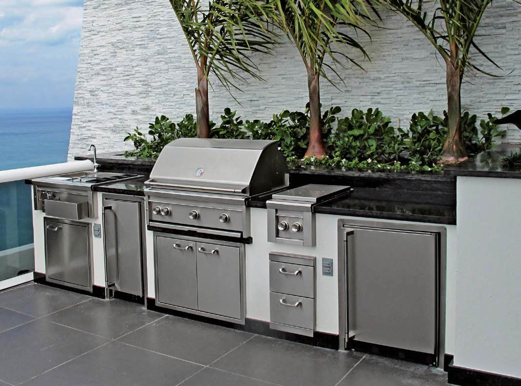 Modish outdoor kitchen featuring a white bar topped by black counters. The stainless steel appliances mix well with the outdoor kitchen's style.