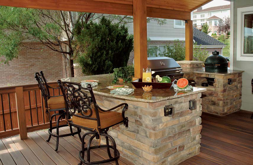 This outdoor kitchen set on the home's deck features a bricks-made bar with smooth marble countertop. The counter provides a small space for a breakfast bar for two.
