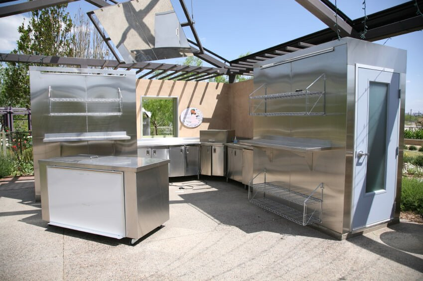 Large outdoor kitchen with stainless steel appliances and bar and counter set.