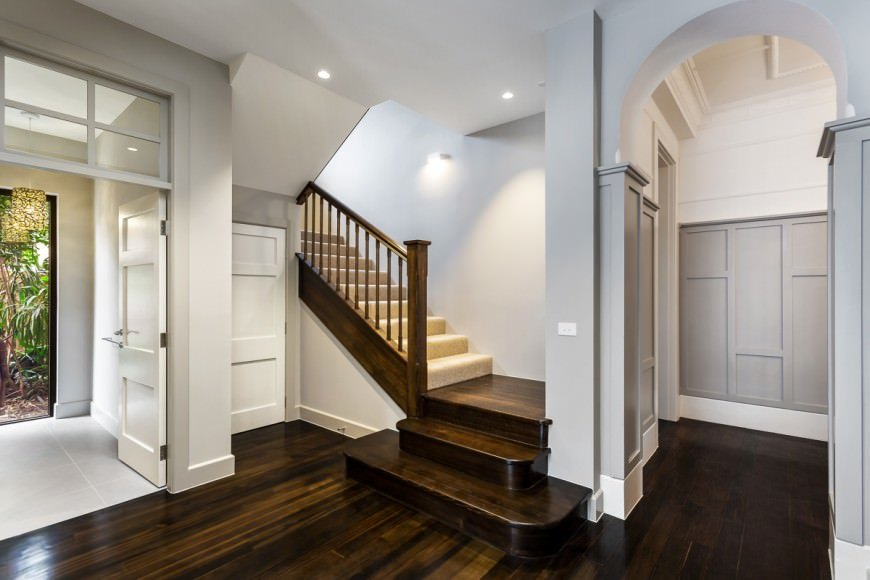 This farmhouse foyer offers a combination of sleek hardwood flooring, light gray walls and white details all over the place.