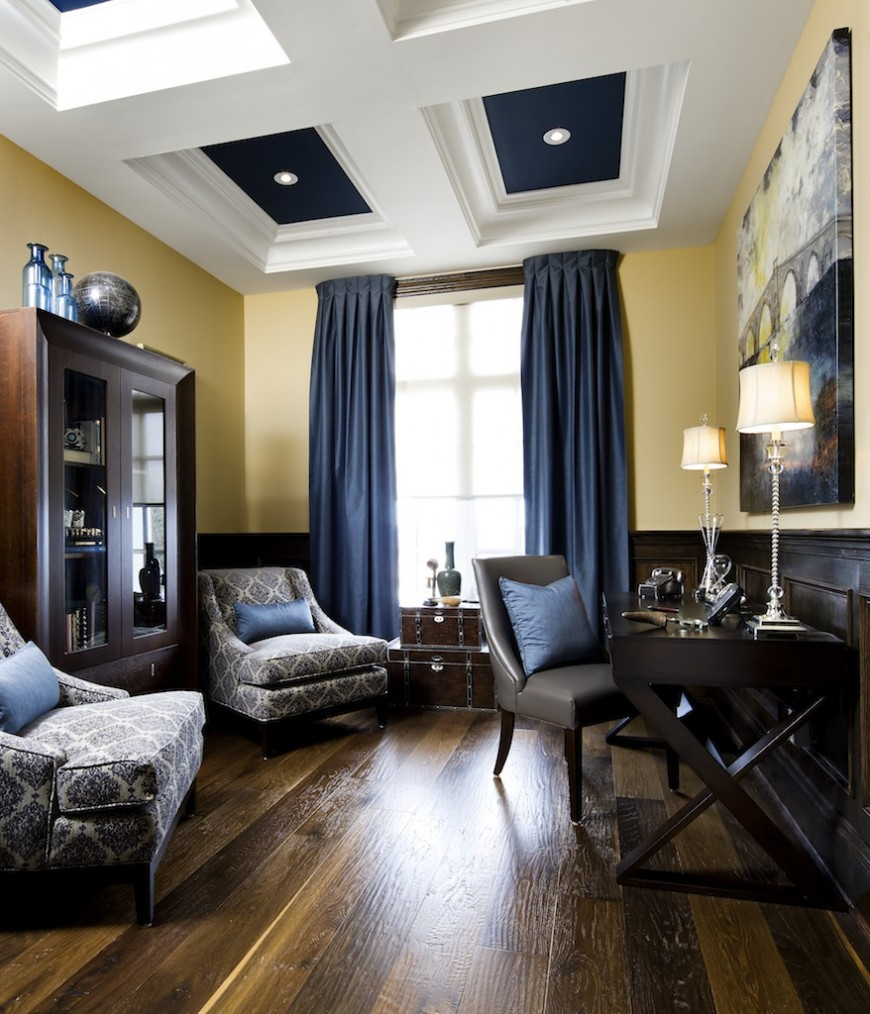 Elegant home office with seating area boasting a pair of blue patterned lounge chairs facing the dark wooden desk that's topped with classy table lamps.