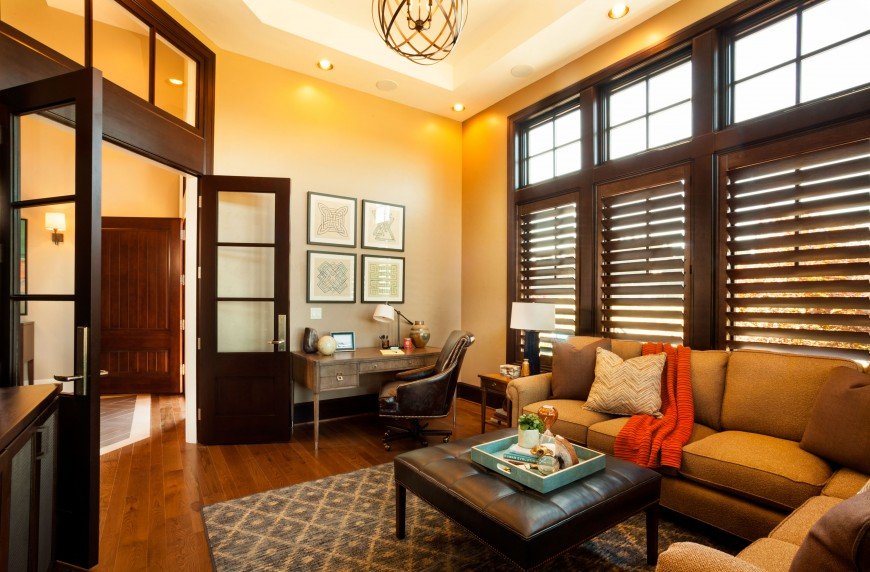 Warm living room offers a corner office decorated with wall arts that are mounted above the wooden desk with brown leather office chair.