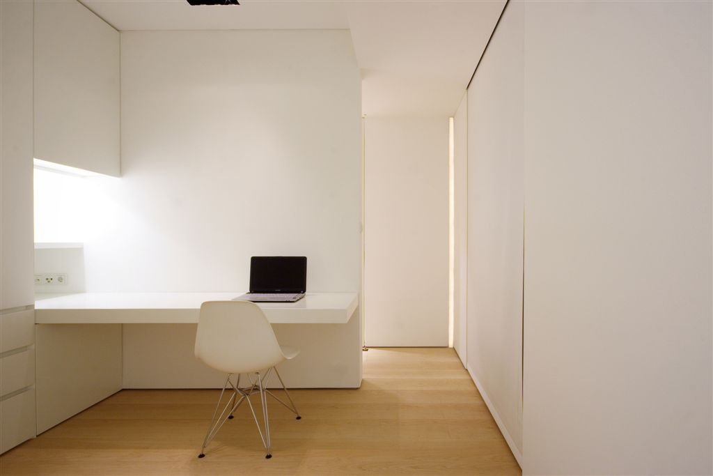 Minimalist home office surrounded with white walls that are fixed with storages and built-in desk paired with a white office chair.