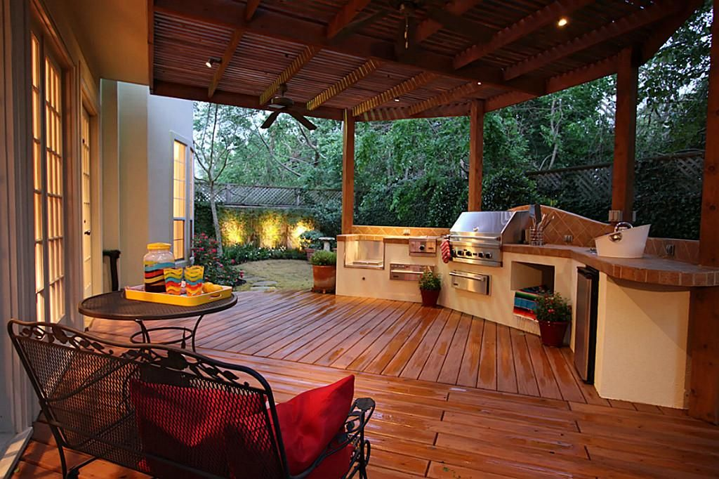 Rustic style outdoor kitchen featuring a nicely done bar counter with stainless steel appliances.
