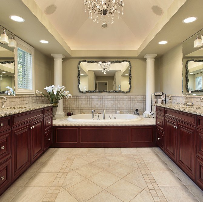 The end-of-the-bathroom columned alcove tub has rich reddish woodwork matching the flanking vanities. The cathedral ceiling creates more space and offers sufficient height for a small chandelier.