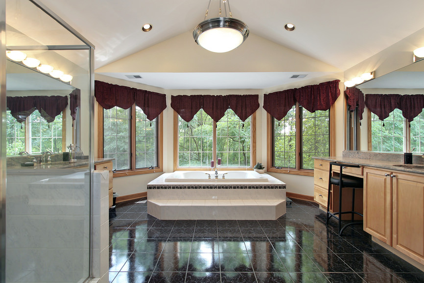 Large master bathroom featuring elegant red window curtains and handsome black tiles flooring, along with a large drop-in tub and a walk-in shower.