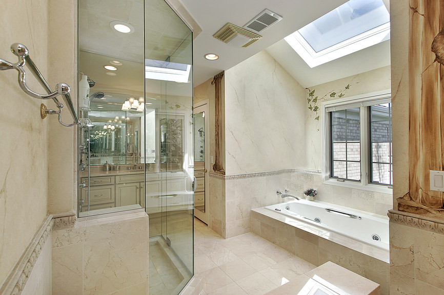 Master bathroom with a drop-in tub and a walk-in shower, along with a ceiling featuring a skylight.