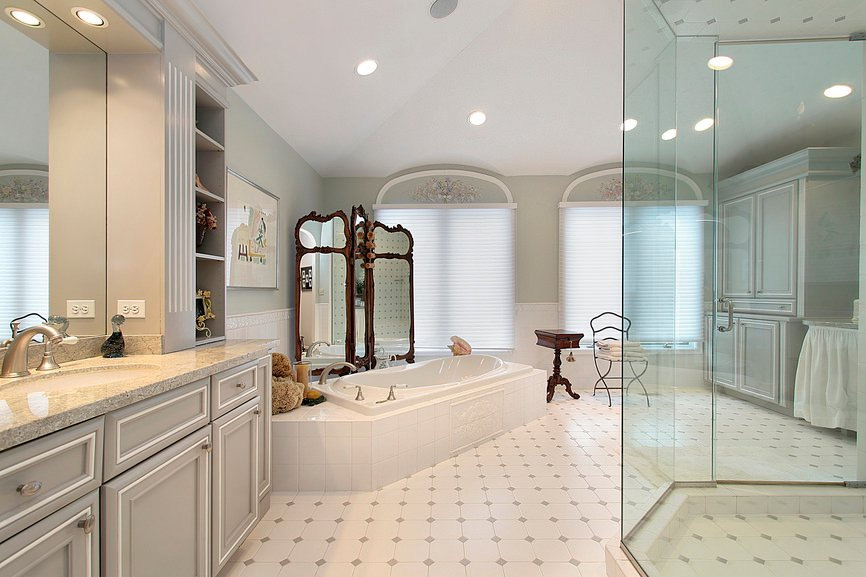 This master bathroom boasts fabulous tiles flooring, a classy drop-in tub and a large walk-in shower.
