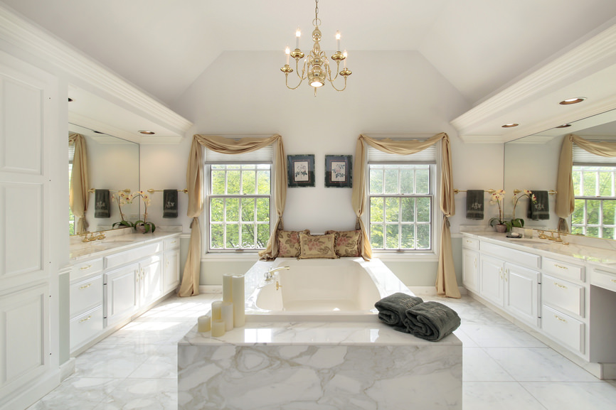 White master bathroom featuring a gorgeous soaking tub and two sink counters lighted by a glamorous chandelier.