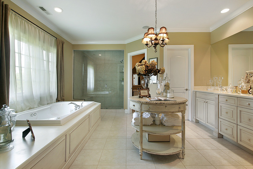 A master bathroom featuring a drop-in tub, a walk-in shower, a classy sink counter and a center table with a gorgeous chandelier just above it.
