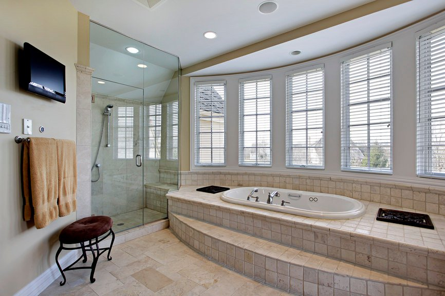 Master bathroom featuring a walk-in corner shower, a deep soaking tub with a tiles platform and a TV on the wall.