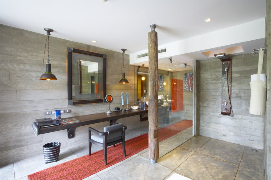 Large and stylish primary bathroom featuring an open shower and a long built-in bathroom counter lighted by pendant lights.