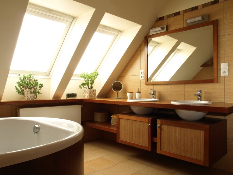 A classy primary bathroom with a stunning shed ceiling with windows. The vessel sinks add class to the room. The bathtub looks perfect together with the bathroom's style.