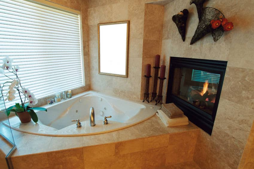 A close up look at this primary bathroom's corner tub with beige tiles platform and walls along with a fireplace.
