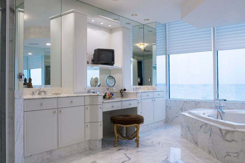 Large master bathroom with marble tiles flooring and countertops. The bathtub's base is also made of marble.