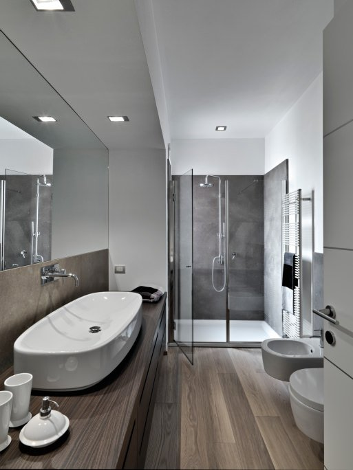 Modern master bathroom offering a walk-in shower room and a large vessel sink set on the hardwood counter matching the hardwood flooring.