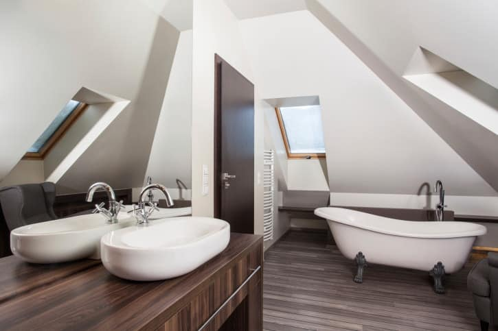 Various wood tone accents encompass this strategically designed bathroom to revolve around three magnificent angled skylights framed in wood. A free standing vintage style bathtub with old fashioned supporting metal feet gives the bathroom a unique twist.