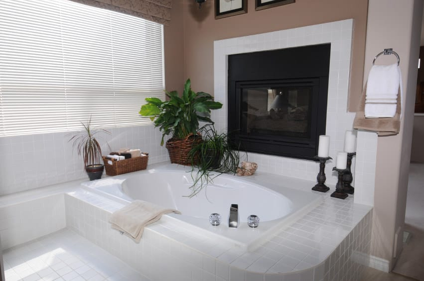 Primary bathroom featuring a bathtub with a white tiles platform along with a fireplace on the side.