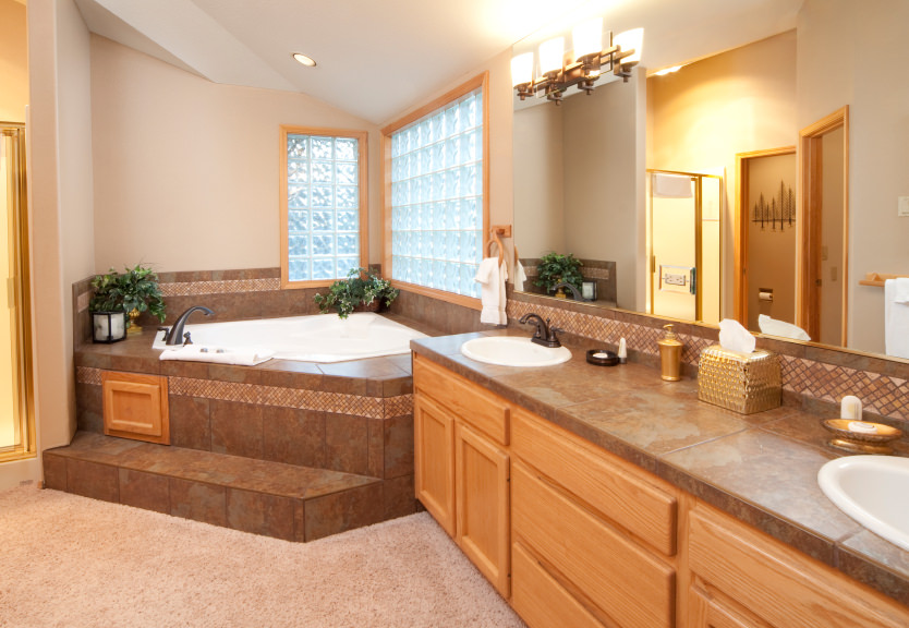 An elegantly-set primary bathroom boasting a very attractive bathtub and an elegant double sink lighted by wall lights. The carpet flooring is just lovely together with the room's style.