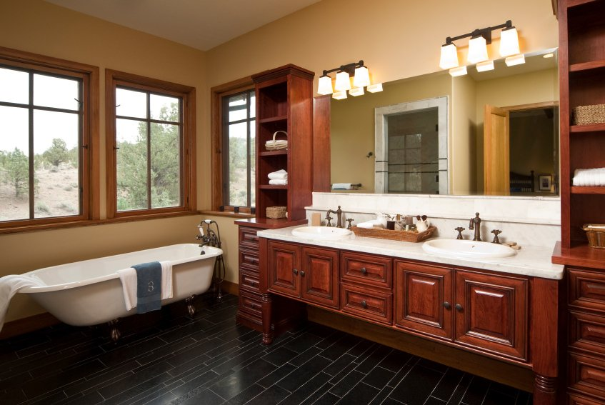This primary bathroom offers a black stylish tiles flooring and brown cabinetry lighted by wall lights. The freestanding tub is located near the windows.