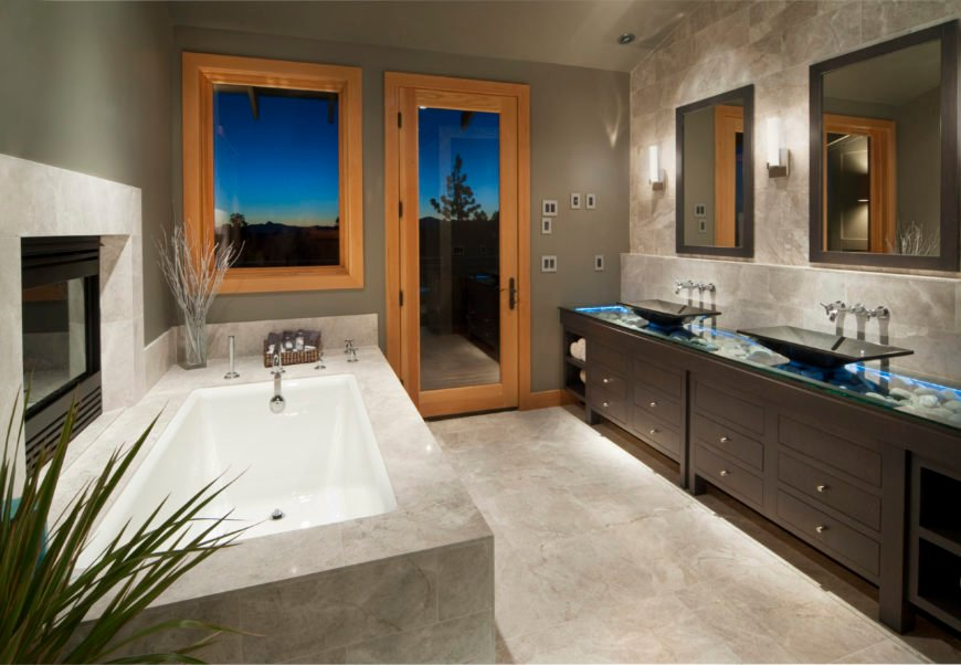 Modern primary bathroom featuring gray walls and tiles flooring, along with black vessel sinks on an attractive sink counter and a large deep soaking tub with a fireplace on the side.
