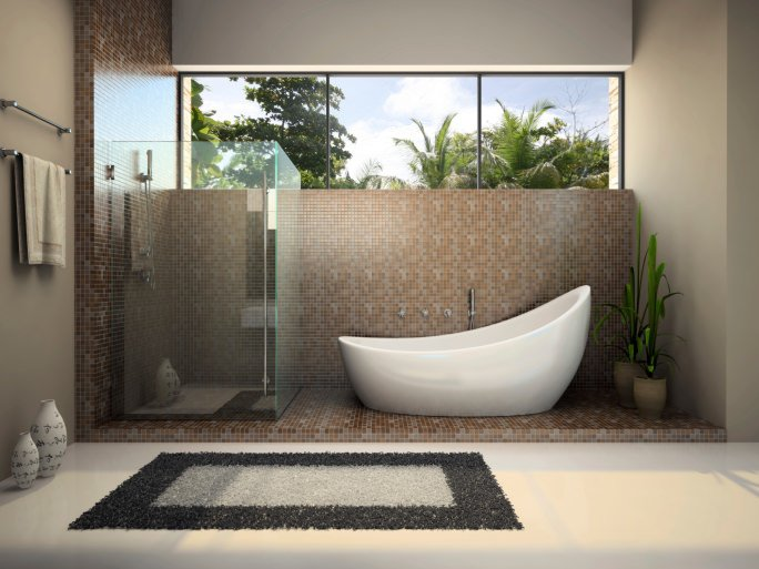 Modern master bathroom with a stylish freestanding tub and a walk-in shower set on the mini-tiles platform surrounded by gray walls and white carpet flooring topped by an area rug.