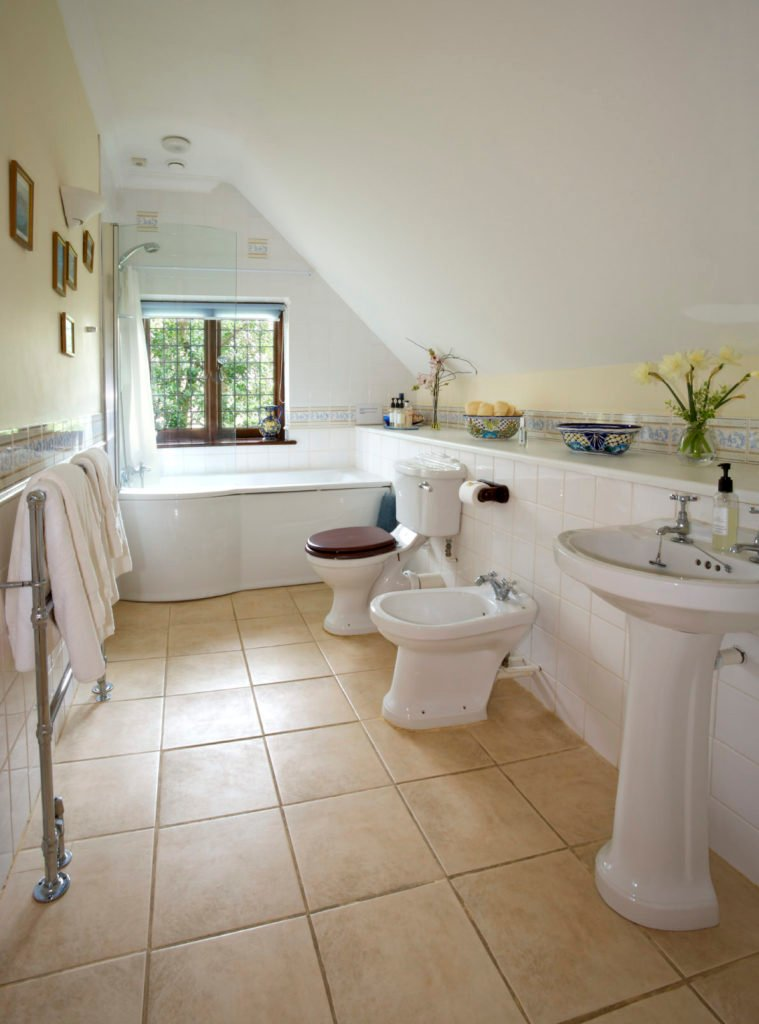 A small primary bathroom featuring a freestanding tub and a pedestal sink along with classy tiles flooring and a shed ceiling.