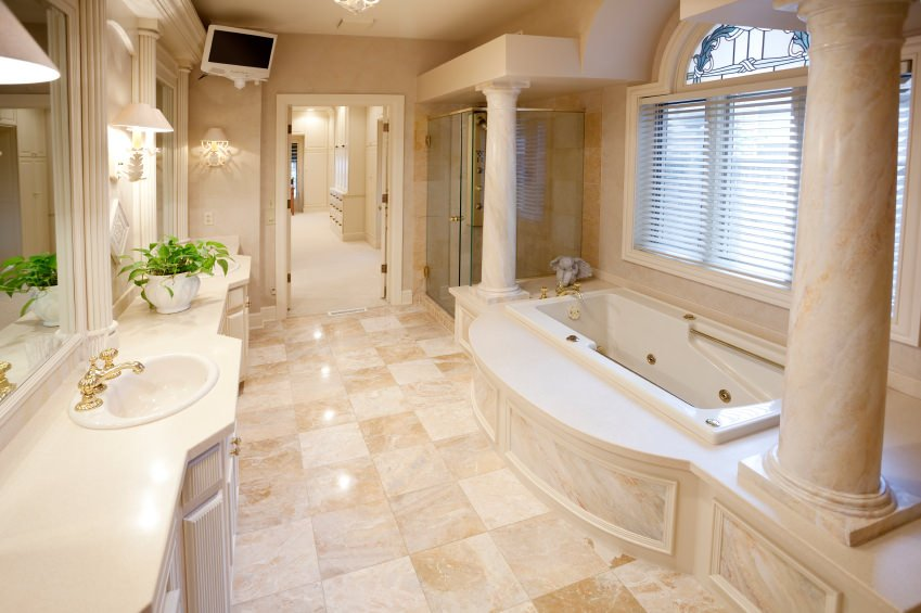 Light beige alcove tub flanked by pillars with the tub under a large window. The alcove is opposite a long two-sink vanity. In the corner is a glass-walled shower. The corner opposite the tub is a wall-mounted TV.