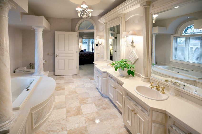 Large master bathroom featuring classy tiles flooring and a gorgeous ceiling and wall lights. The bathtub looks very elegant together with the bathroom counter with two sinks.
