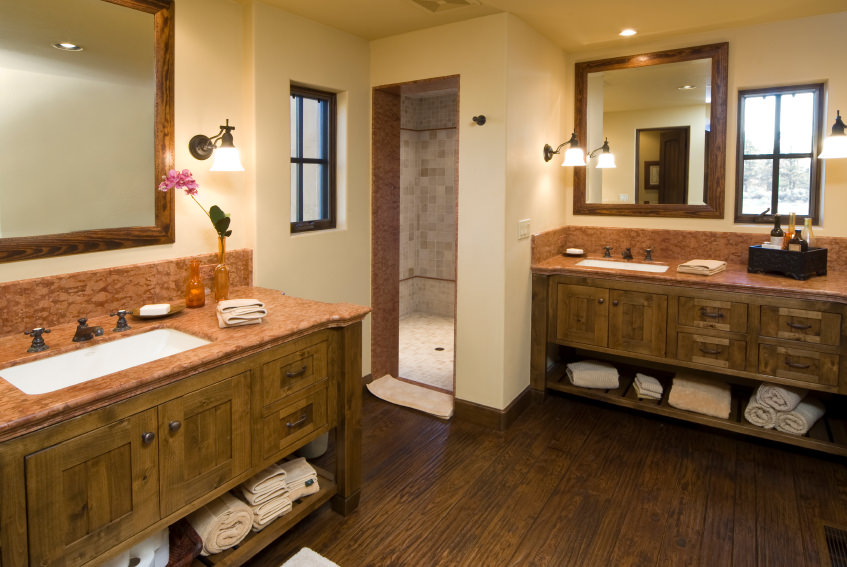 Master bathroom featuring a shower room and sink counters with classy countertops lighted by wall lights. The room has hardwood floors and white walls.