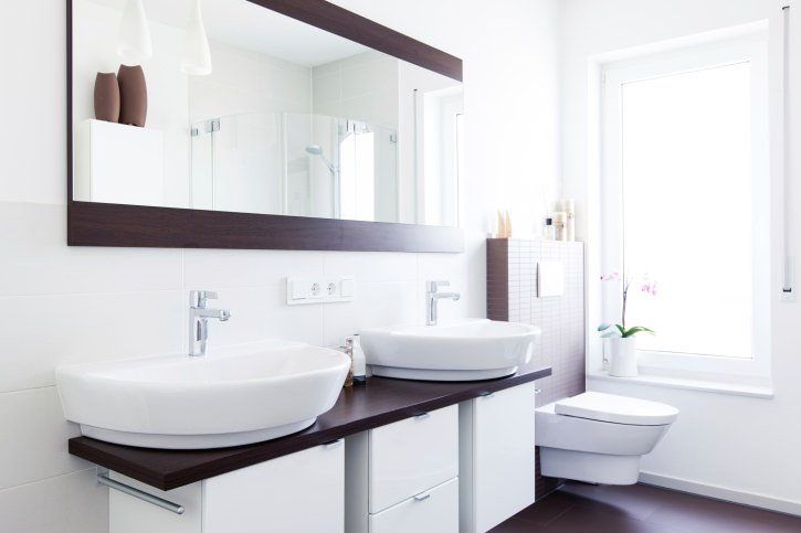 A bold contrast creates the beauty of this modern sleek bathroom. Dark wood counter tops and flooring compliment the white ceramic bowl styled twin sink basins and polished chrome fixtures. Clean white walls and a polished white modern shaped ceramic toilet basin seal the deal for this contemporary washroom.