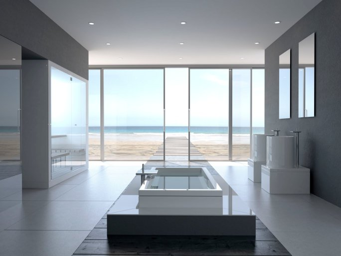 Modern master bathroom with a stylish drop-in tub and a pair of sinks surrounded by gray walls and a regular white ceiling lighted by recessed lights. There's a doorway leading straight to the seaside.