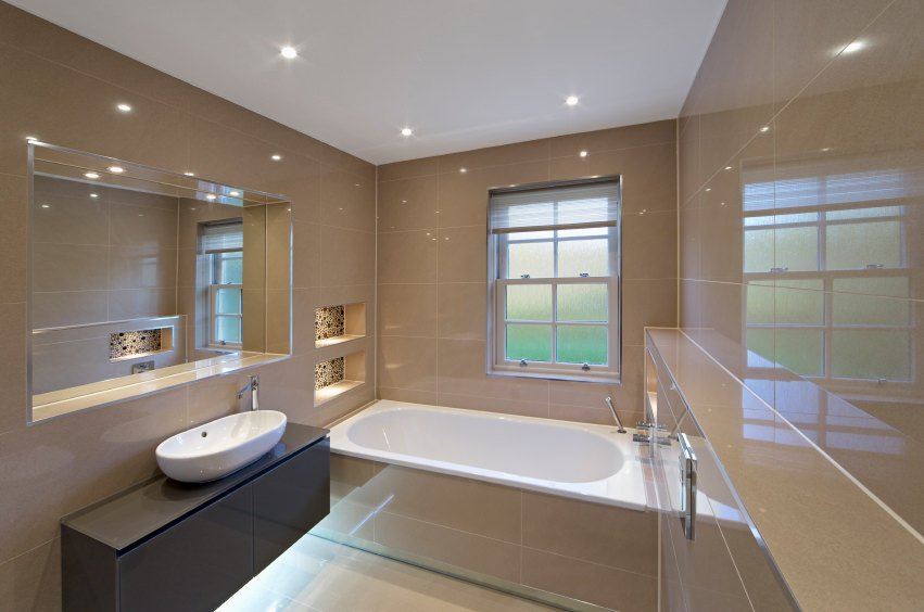A primary bathroom surrounded by brown tiles walls and is lighted by recessed ceiling lights. The room offers a drop-in tub and a floating vanity with a vessel sink.